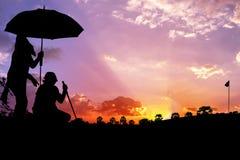 Homme de silhouette avec des caddies jouant le golf Photographie stock libre de droits