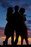 Homme de silhouette entre le coucher du soleil de deux femmes Photographie stock libre de droits