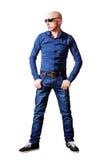 Homme de skinhead dans les lunettes de soleil et des blues-jean Photo stock