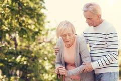 Homme de soin agréable aidant son épouse Image libre de droits