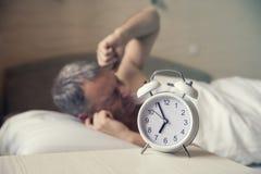 Homme de sommeil troublé par début de la matinée de réveil Homme fâché dans le lit réveillé par un bruit Images stock