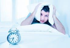 Homme de sommeil troublé par le mornin tôt de réveil Photo stock