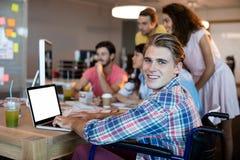 Homme de sourire à l'aide de l'ordinateur portable tout en travaillant avec son équipe dans le bureau Photos libres de droits