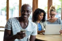 Homme de sourire à l'aide du téléphone portable dans le café Images stock