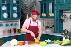 Homme de sourire à la cuisine coupant le paprika jaune dans le tablier et le chapeau Photos libres de droits