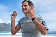 Homme de sourire écoutant la musique sur des écouteurs Images stock