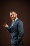 Homme de sourire élégant avec la barbe tenant le tuyau de tabagisme images stock
