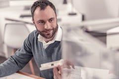Homme de sourire adulte barbu travaillant au bureau images stock