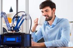 Homme de sourire agréable à l'aide de l'imprimante 3d Photos stock