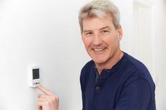 Homme de sourire ajustant le thermostat sur le système de chauffage domestique photo libre de droits