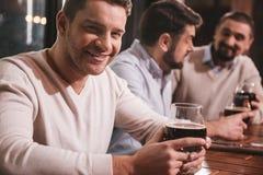 Homme de sourire attirant s'asseyant avec ses amis à la table Photo libre de droits