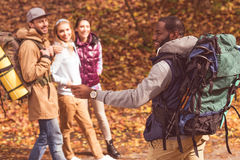 Homme de sourire avec des amis dans la forêt d'automne Photos stock