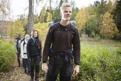 Homme de sourire avec des amis trimardant sur Forest Trail Photographie stock libre de droits