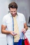Homme de sourire avec des paniers utilisant le smartphone Photo libre de droits