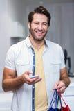Homme de sourire avec des paniers utilisant le smartphone Images libres de droits