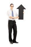 Homme de sourire avec des verres tenant une grande flèche noire se dirigeant  Photos libres de droits