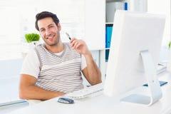 Homme de sourire avec l'ordinateur dans un bureau lumineux photographie stock libre de droits