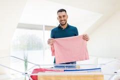 Homme de sourire avec la blanchisserie et le support de séchage à la maison images stock