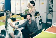 Homme de sourire avec la famille choisissant la machine à laver Photo stock