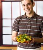 Homme de sourire avec la plaque de salade image stock