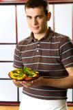 Homme de sourire avec la plaque de salade Photos libres de droits