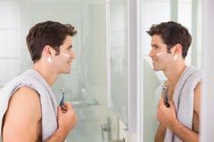 Homme de sourire avec la réflexion rasant dans la salle de bains Images libres de droits