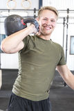 Homme de sourire avec le kettlebell au gymnase de forme physique Photographie stock libre de droits