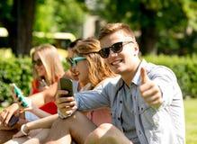 Homme de sourire avec le smartphone montrant des pouces  Photo stock
