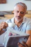 Homme de sourire ayant la tasse du journal de lecture de café Images libres de droits