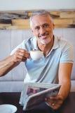 Homme de sourire ayant la tasse du journal de lecture de café Image libre de droits