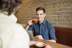 Homme de sourire ayant le café au café Photo stock