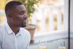 Homme de sourire ayant le vin pendant le déjeuner Images stock
