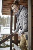 Homme de sourire barbu avec des verres et position chaude d'habillement sur le porche d'une maison en bois avec ses mains dans le images stock