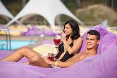 Homme de sourire bel détendant avec l'amie près de la piscine sur les canapés amortis avec des boissons au lieu de villégiature l Image stock