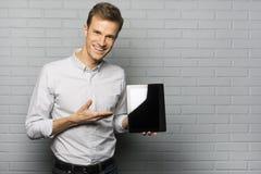 Homme de sourire bel montrant un PC de Tablette, d'isolement au-dessus d'un b gris images libres de droits