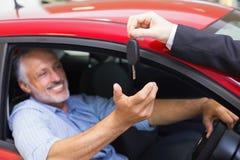 Homme de sourire conduisant une voiture tandis que vendeur sa clé donnante photo stock