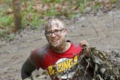 Homme de sourire couvert de boue rampant sous un filet de camouflage photographie stock