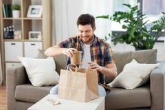 Homme de sourire déballant les plats à emporter à la maison images stock