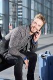 Homme de sourire détendant à l'aéroport avec le téléphone portable et le sac Images stock
