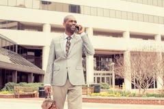 Homme de sourire d'affaires parlant au téléphone portable tenant la serviette descendant la rue Images stock