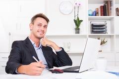 Homme de sourire d'affaires travaillant sur l'ordinateur portable au bureau photo stock