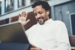 Homme de sourire d'Afro-américain dans des écouteurs faisant l'appel visuel à la rue ensoleillée sur le pavé tactile électronique Photos libres de droits