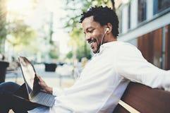 Homme de sourire d'Afro-américain dans des écouteurs faisant la conversation visuelle dehors sur le pavé tactile électronique, vé Photographie stock