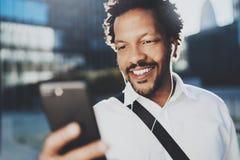 Homme de sourire d'Afro-américain dans l'écouteur faisant l'appel visuel par l'intermédiaire du téléphone portable disponible Con Photos libres de droits