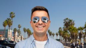 Homme de sourire dans des lunettes de soleil au-dessus de plage de Venise photo libre de droits