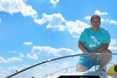 Homme de sourire dans des vêtements bleus dans un bateau sur un fond de l'eau lisse d'un ciel nuageux bleu photographie stock