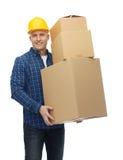 Homme de sourire dans le casque avec des boîtes en carton Images stock