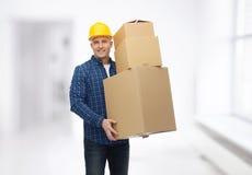 Homme de sourire dans le casque avec des boîtes en carton Photographie stock