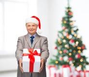 Homme de sourire dans le costume et chapeau d'aide de Santa avec le cadeau Photo libre de droits