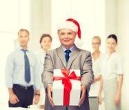 Homme de sourire dans le costume et chapeau d'aide de Santa avec le cadeau Image libre de droits